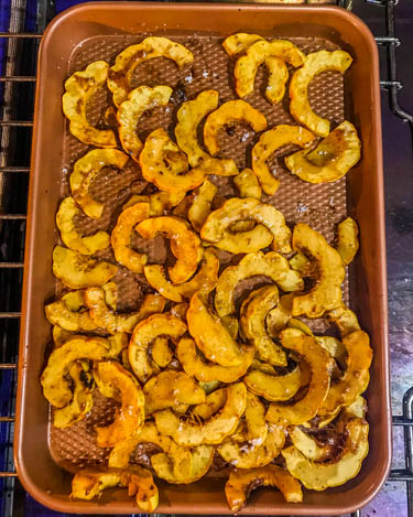 The delicata squash after it is roasted with the glaze on a baking sheet.
