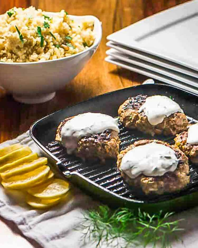 4 ground lamb patties topped with dill-yogurt sauce on a grill pan along side lemon slices and bulgar pilaf.