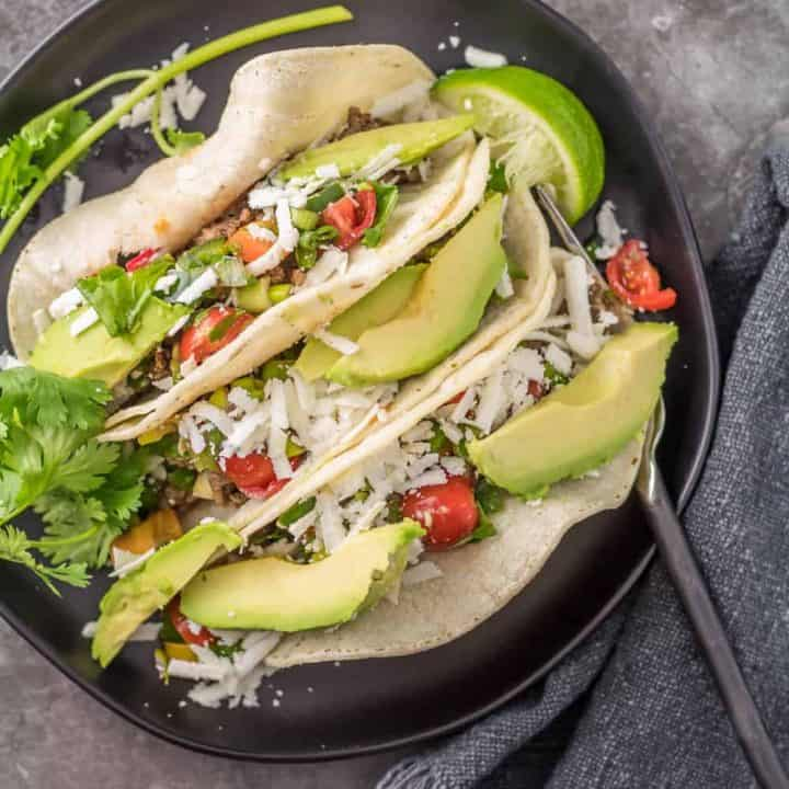 Easy Ground Lamb Tacos in a corn tortilla with pico de gallo and avocado on a round black plate with a black fork.
