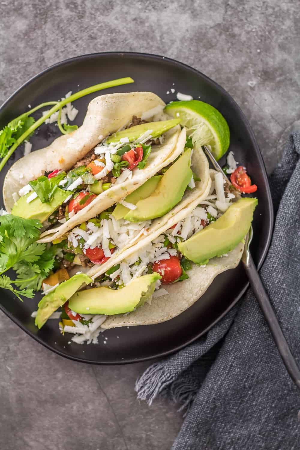 Gluten free Easy Ground Lamb Tacos featuring spiced ground lamb, salsa, cotija, avocado on a black ceramic plate with a black fork and grey napkin.