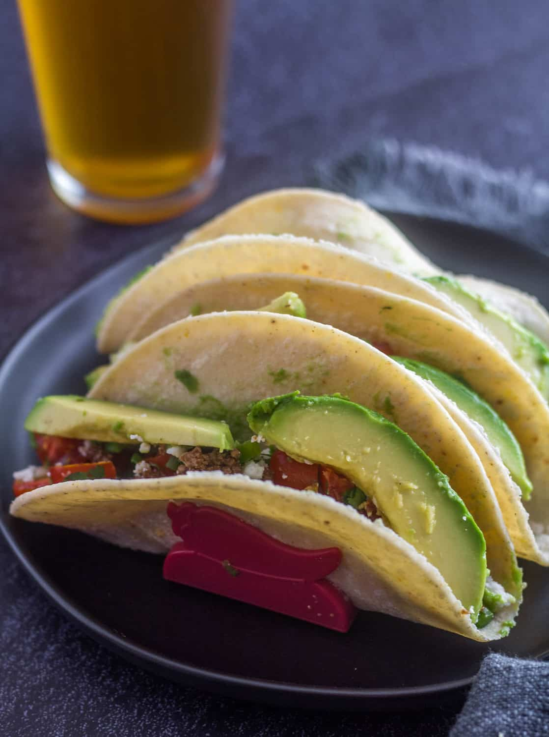 Easy Ground Lamb Tacos in a corn tortilla with pico de gallo and avocado on a round black plate with a black fork... a glass of beer in the background.