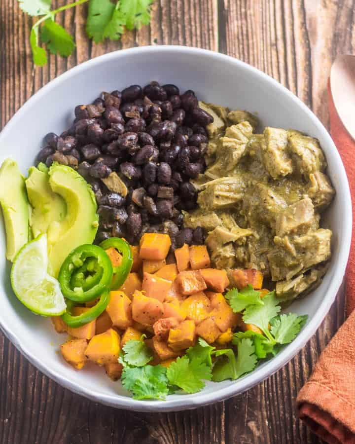 A white ceramic bowl of healthy mole verde with roasted butternut squash, black beans, and avocado.