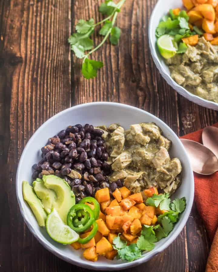 2 healthy mole verde bowls with garnishes on a wood background with orange napkin and copper forks.