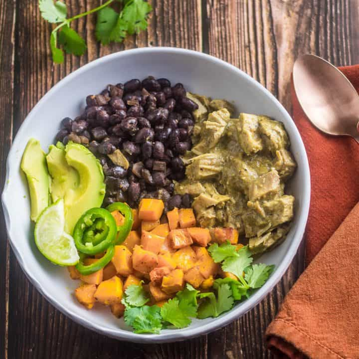 A healthy mole verde bowl with leftover turkey, roasted butternut squash, black beans, avocado, jalapeno, cilantro, in a white bowl with copper spoon.
