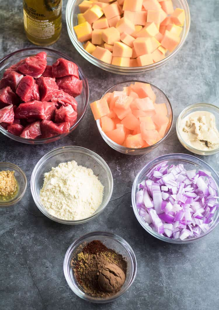 Ingredients for Instant Pot Lamb Butternut Squash Stew: butternut squash, bell pepper, tahini, chopped red onion, spices, instant masa, garlic, cubed lamb, beer.