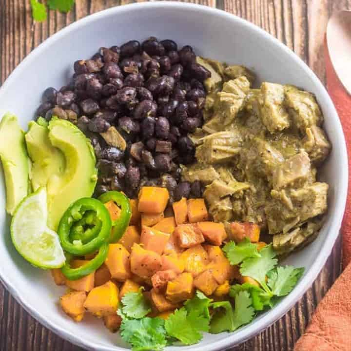 Healthy Mole Verde Bowls with leftover turkey in mole verde, quick black beans, roasted butternuts squash, avocado slices, and cilantro sprigs in a white ceramic bowl with copper spoon and orange napkin.