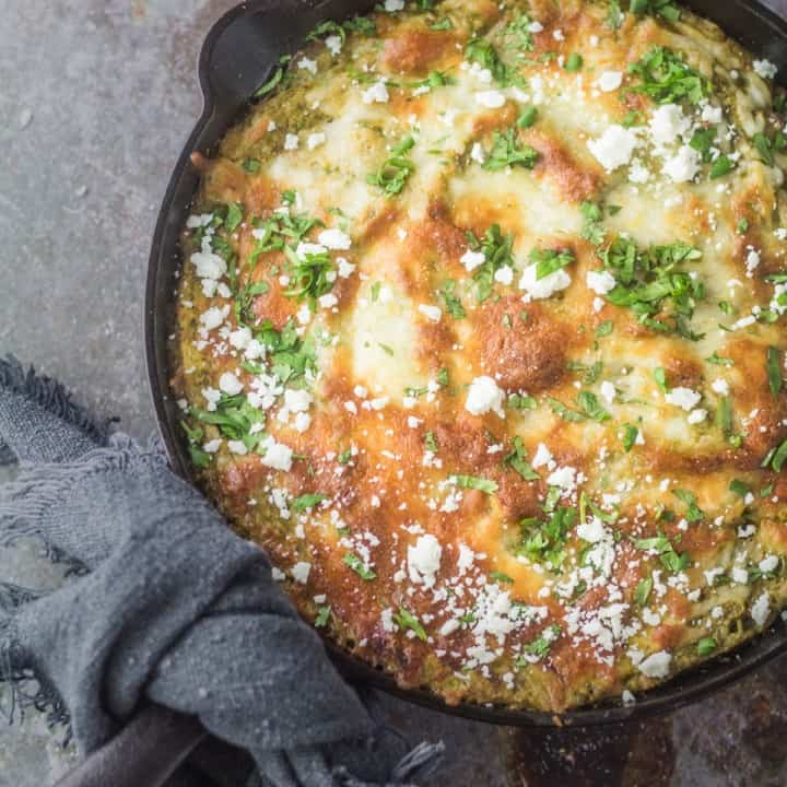 Quick ground lamb enchilada casserole with a zesty salsa verde avocado spinach filling layered with corn tortillas and Mexican cheese in a cast iron skillet.
