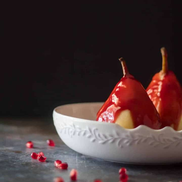 2 spiced tequila poached pears with orange pomegranate sauce in a white ceramic bowl with a black background.