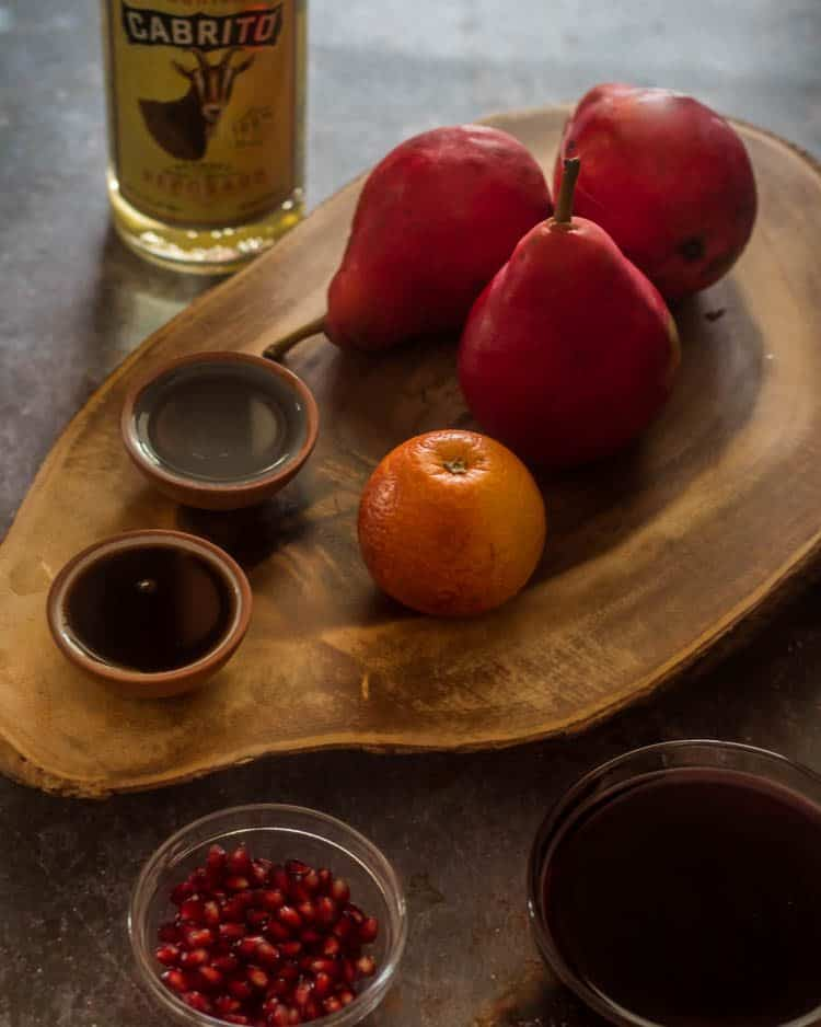 Ingredients for spiced tequila poached pears on a wood cutting board.