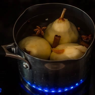 pears with whole spices in the tequila poaching liquid on an induction stove.