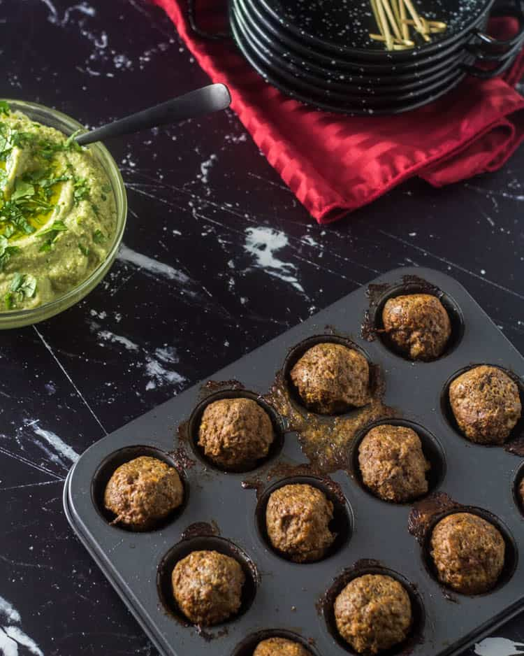 Baked lamb meatballs in a mini muffin tin next to a bowl of avocado hummus.