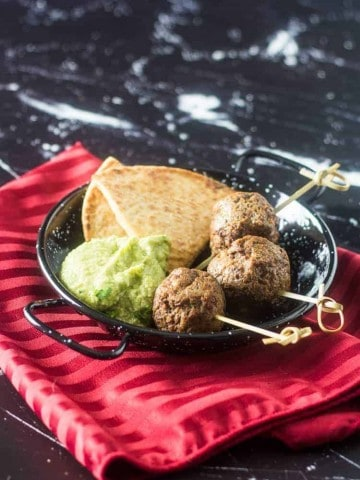 A black and white speckled mini paella pan with 3 meatballs, a scoop of avocado hummus, and pita bread.