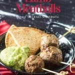 A red napkin with black and white speckled plate with 3 meatballs, a scoop of avocado hummus, and toasted pita.