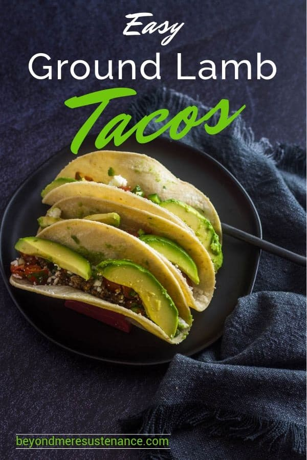 Easy Ground Lamb Tacos featuring pico de gallo, avocado, and cotija in a corn tortilla on a black plate with grey napkin. Gluten free and delicious!