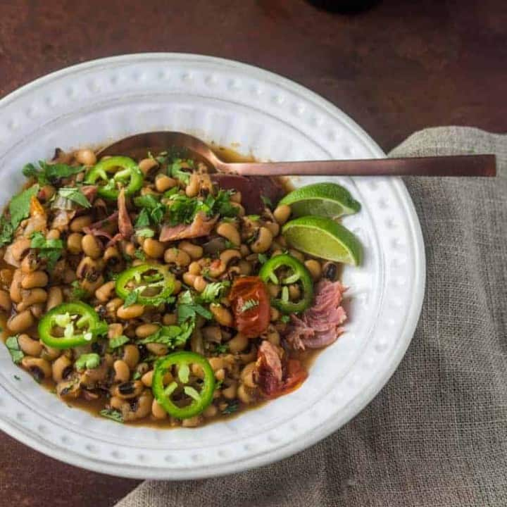 A bird's eye view of instant pot black eyed peas in a white bowl with a copper spoon and linen napkin.