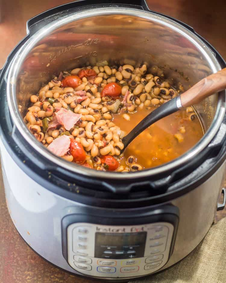 The borracho style black eyed peas are cooked and ready to serve with a wood handled ladle.