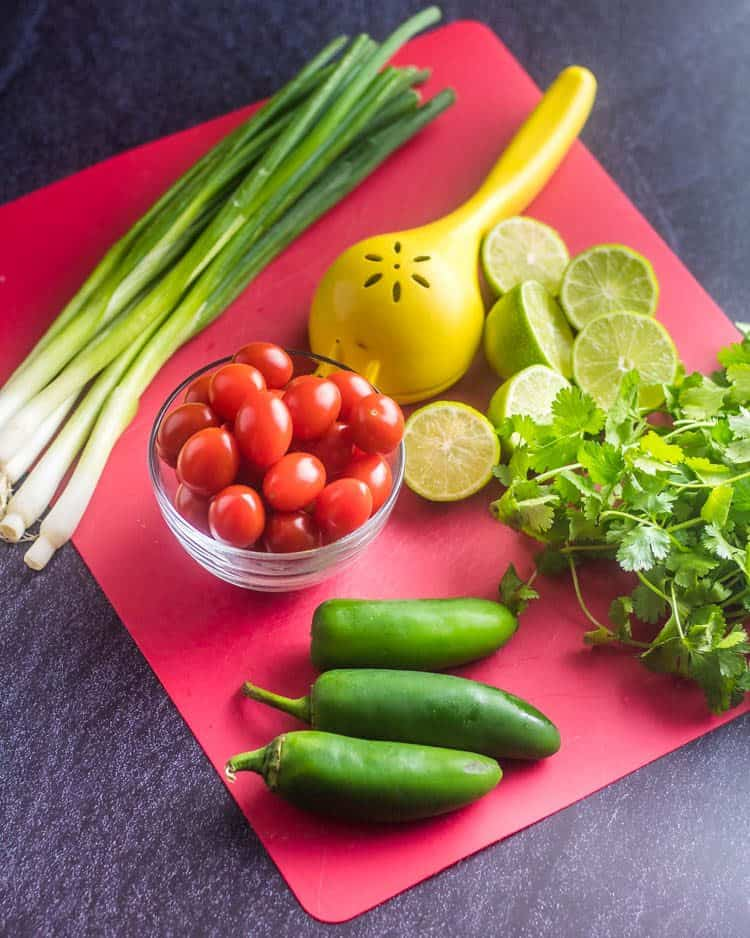 A red cutting mat with ingredients for Fresh Pico de Gallo Salsa: scallions, tomatoes, halved limes and squeezer, a bunch of cilantro, and 3 jalapeños.