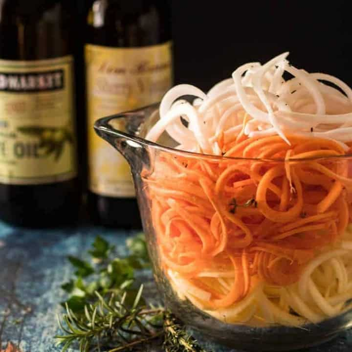 An 8 cup glass bowl with spiralized turnips, sweet potatoes, and rutabagas.