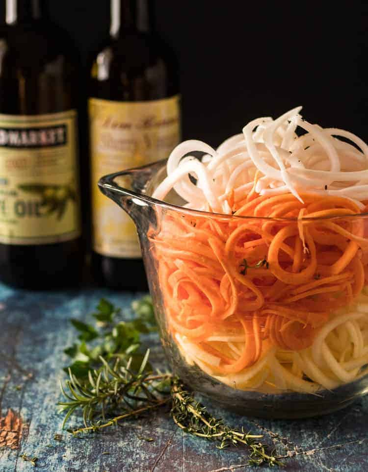 An 8 cup glass bowl with spiralized turnips, sweet potatoes, and rutabagas, fresh rosemary, thyme, and parsley, and sherry vinegar and olive oil in the background.