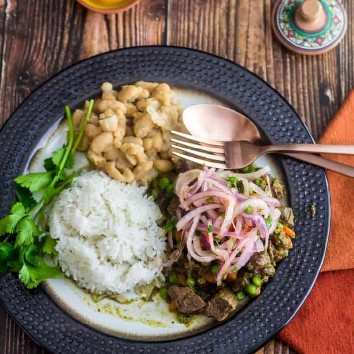 A pin of a plate of Peruvian lamb stew (seco de cordero) with a copper fork and orange napkin.