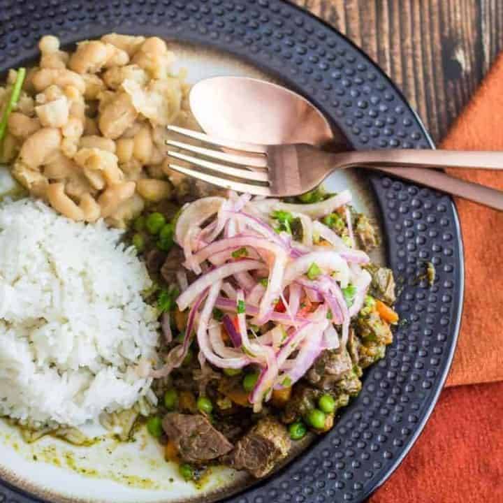 A bronze rimmed plate with Slow Cooker Peruvian Lamb Stew - Seco de Corder - with white rice and seasoned white beans, copper flatware, a tiny bowl of ají amarillo, Peruvian salt, and an orange napkin.