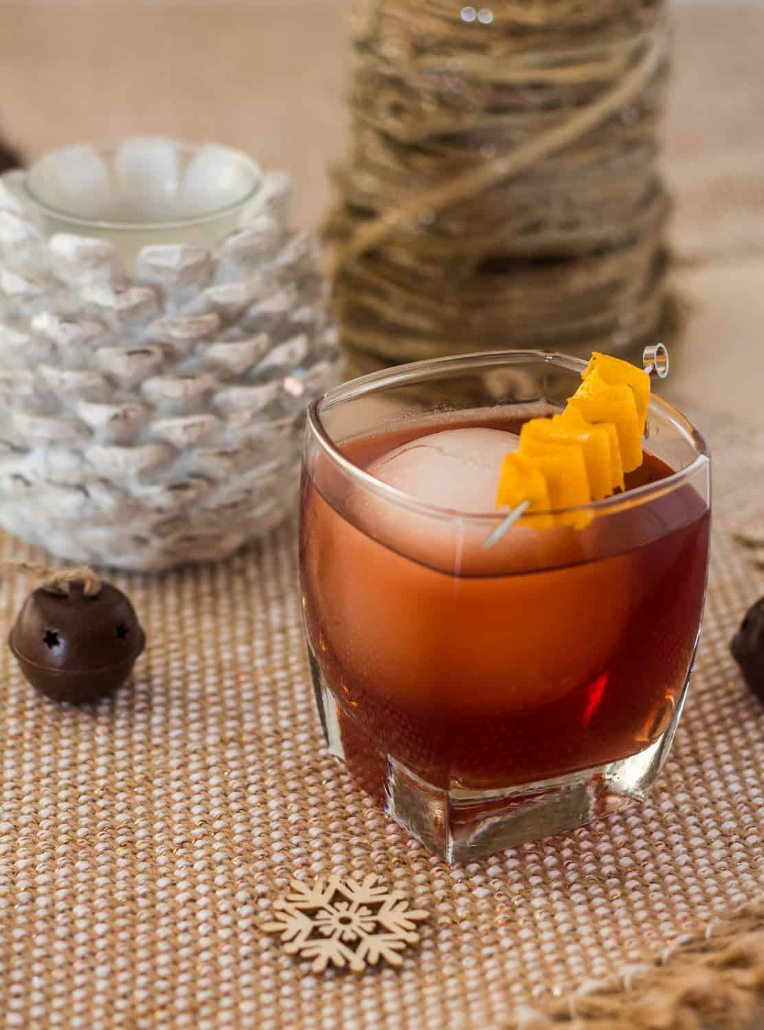 A single Winter Old Fashioned whiskey cocktail on a sparkly burlap tablerunner with christmas ornaments and candle.
