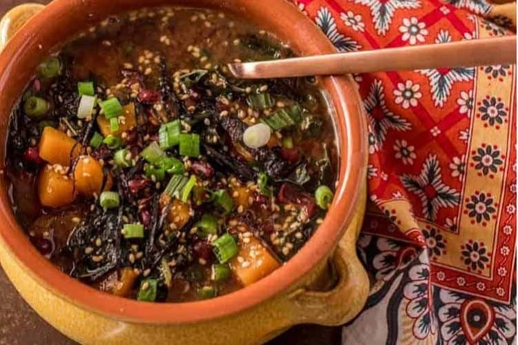Instant Pot Adzuki Bean Soup Close Up with squash, scallions, kale in a terra cotta bowl with copper spoon.