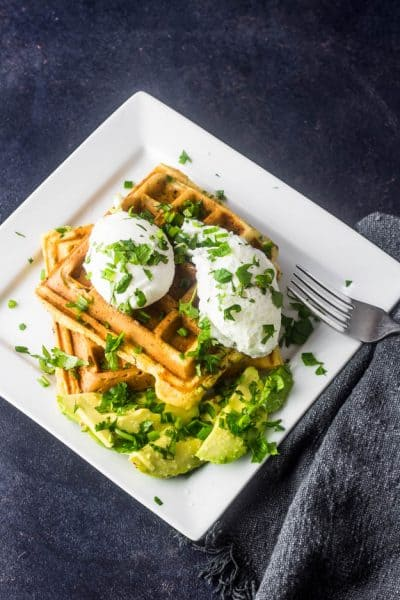 A white square plate with 2 savory chorizo cornbread waffles topped with 2 poached eggs, sliced avocado, and chopped cilantro.