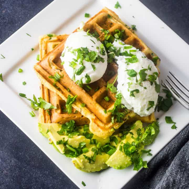 2 savory chorizo cornbread waffles on a white square plate topped with 2 poached eggs, sliced avocado, and chopped cilantro.