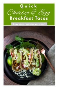 A Pinterest pin with a plate of chorizo and egg tacos, garnishes, copper fork, and grey napkin.