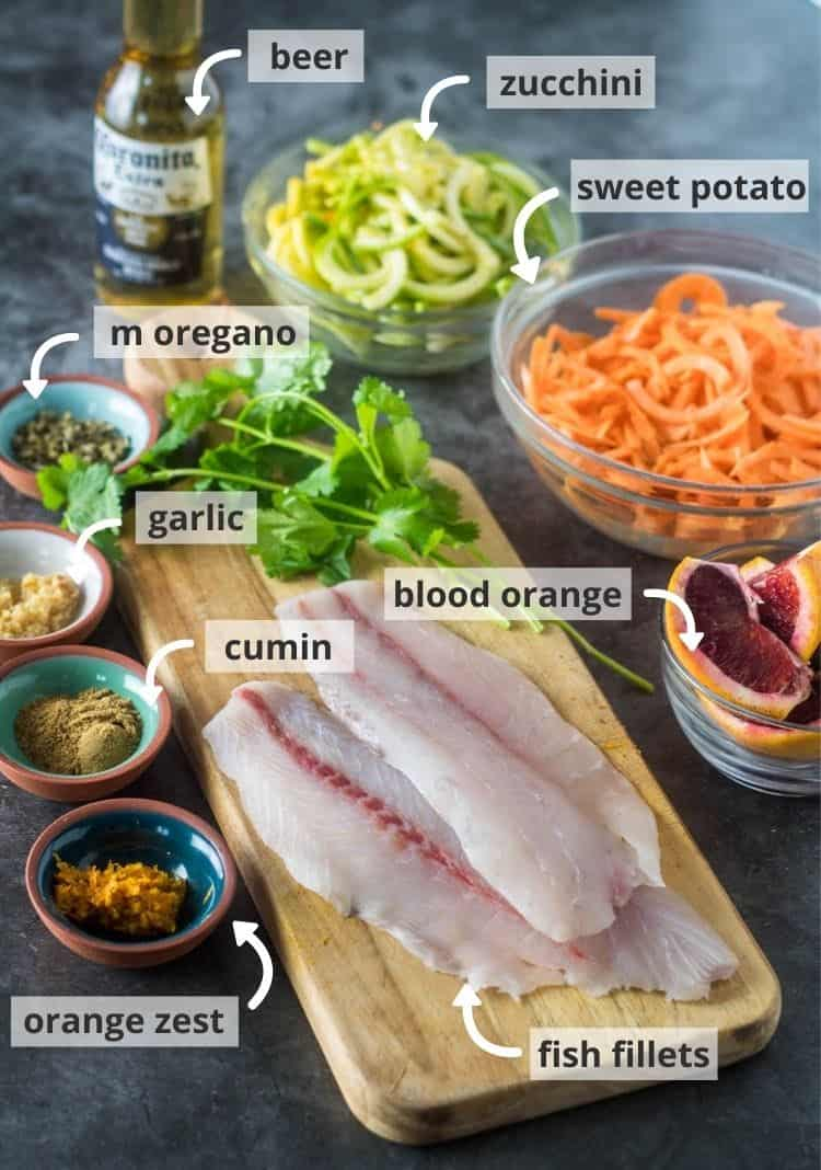 Ingredients for Healthy Mexican Fish in Blood Orange Broth in prep bowls on a wood cutting board.