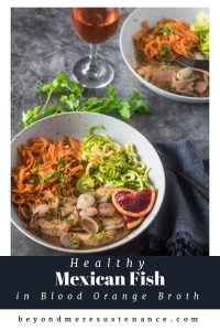 A grey shallow bowl with barramundi and spiralized sweet potato and grey squash in a blood orange and beer broth garnished with blood orange slice.