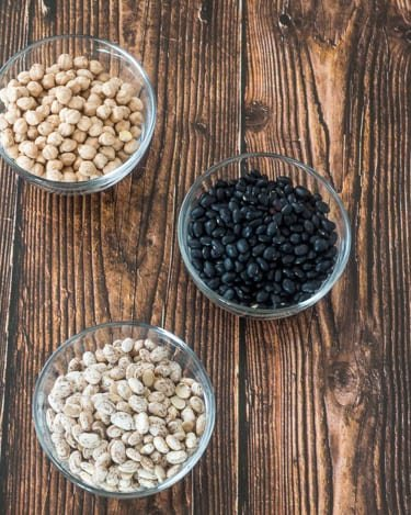 Chick peas, black beans, and pinto beans in glass bowls before they're cooked.
