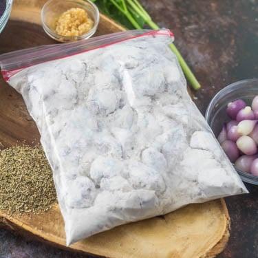 A zip bag with cubed lamb, flour, salt, pepper.
