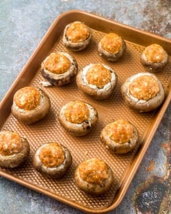 A copper tray with the uncooked mushroom caps stuffed with chorizo-turkey meatball mixture.
