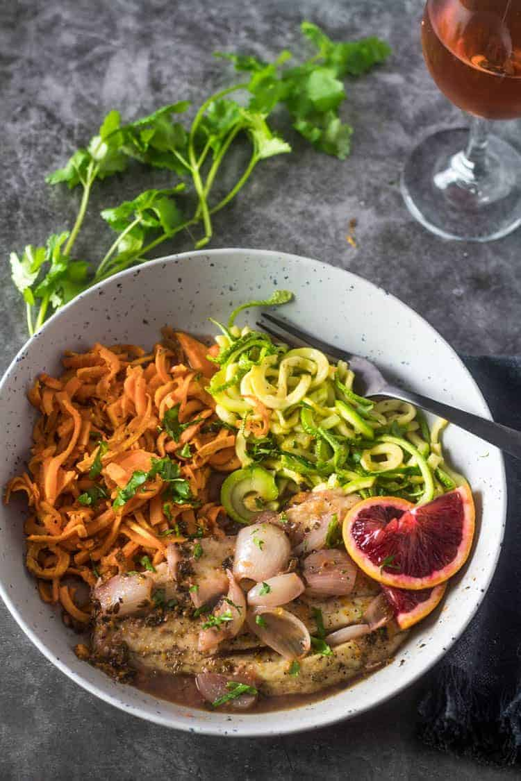 A grey shallow bowl with healthy Mexican fish - barramundi and spiralized sweet potato and grey squash in a blood orange and beer broth garnished with blood orange slice.
