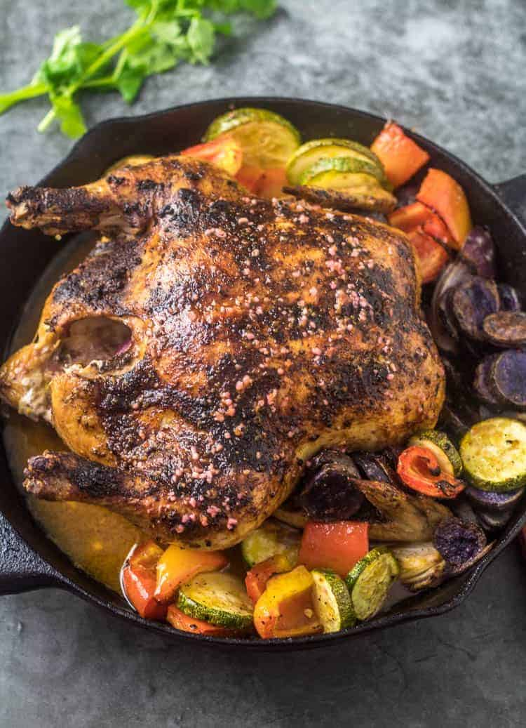 Mexican Roasted Chicken and Vegetables in a black cast iron skillet with cilantro garnish on a grey background.