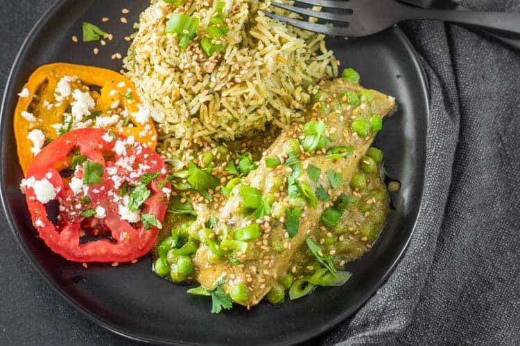 Mexican Salmon in Mole Verde (Pipian) in a black plate with cilantro rice and sliced heirloom tomatoes.