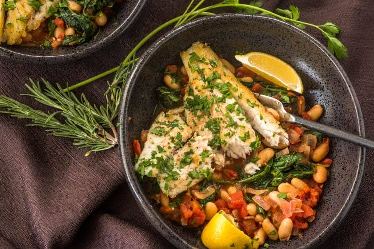 Tuscan Fish With Cannelini Beans, Tomatoes, & Spinach in a black ceramic bowl with lemon wedges.