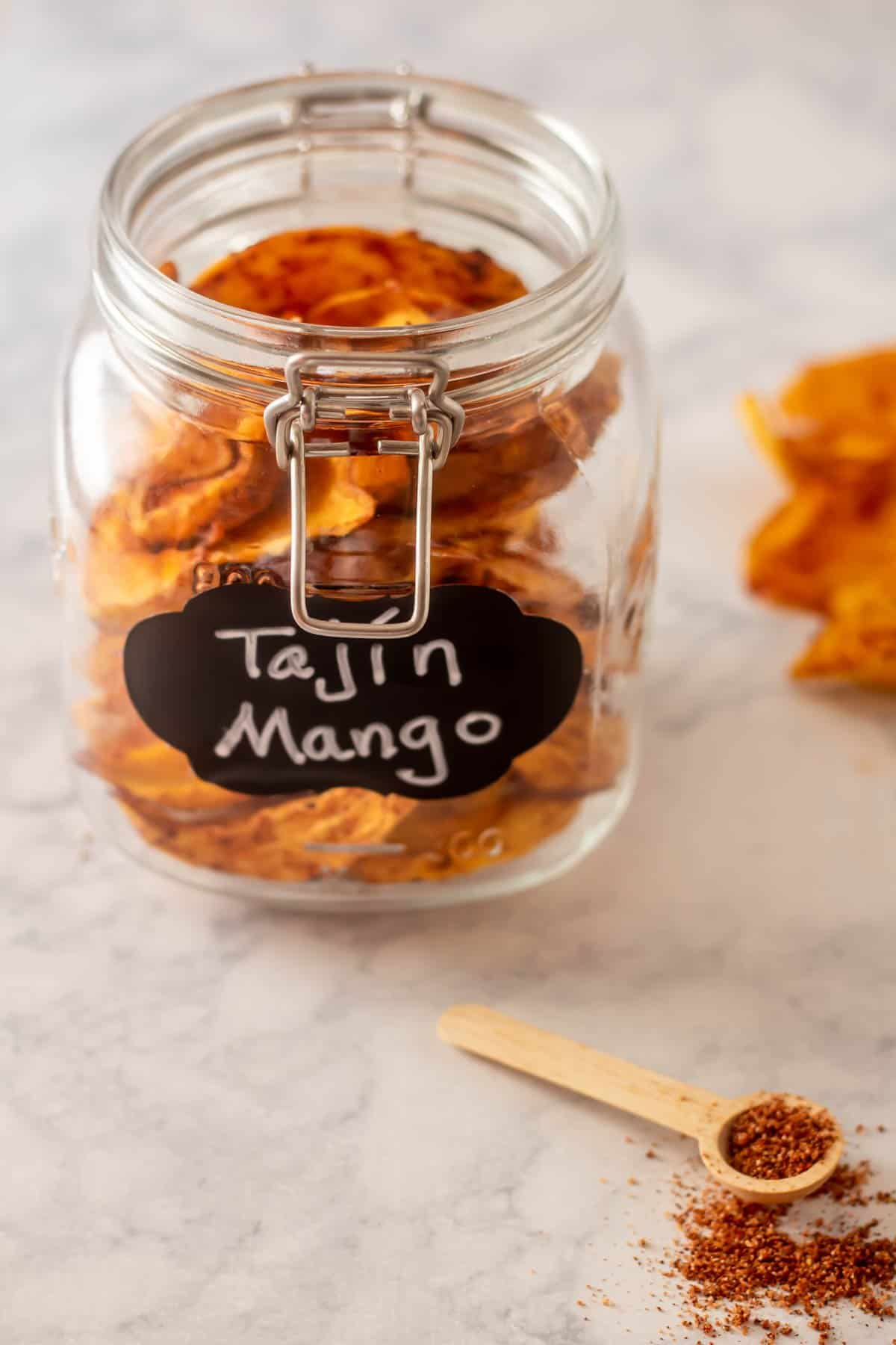 A jar of dehydrated tajin mangoes with a chalkboard label on a marble surface.