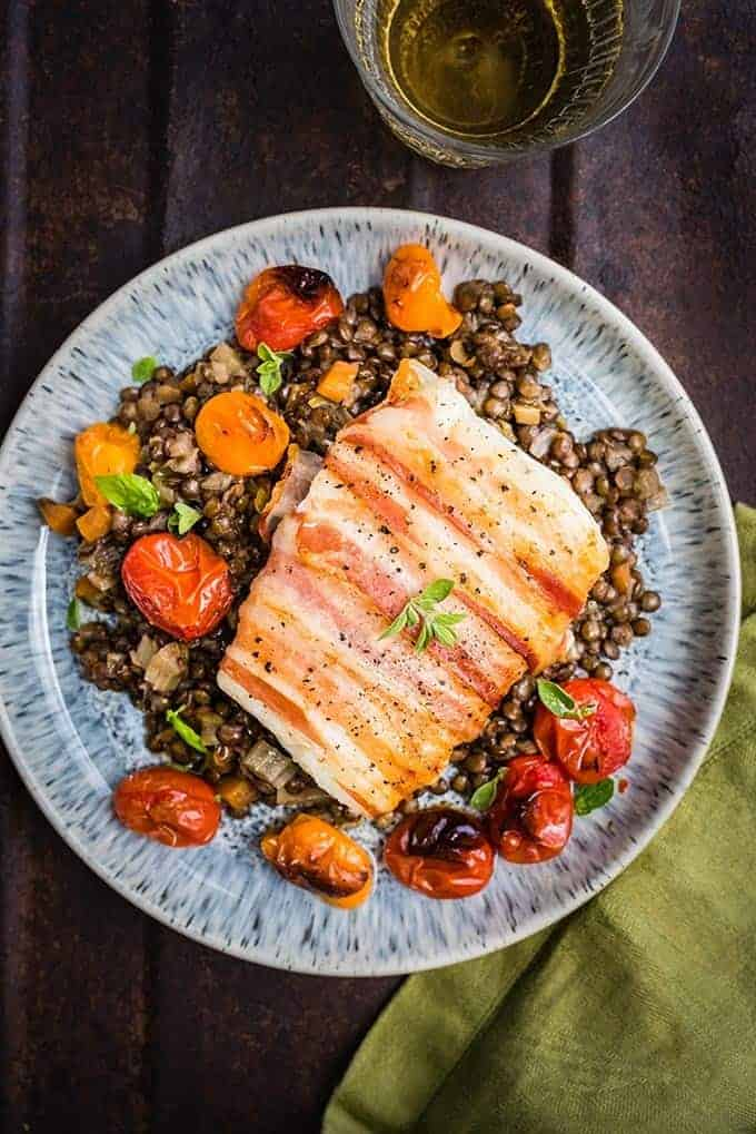 Pancetta-wrapped cod with blistered tomatoes and lentils