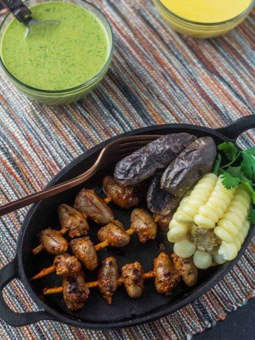 An oval cast iron plate with 3 Peruvian chicken anticuchos alongside roasted purple potatoes, choclo (giant corn), and 2 sauces - aji verde and rocoto aioli.