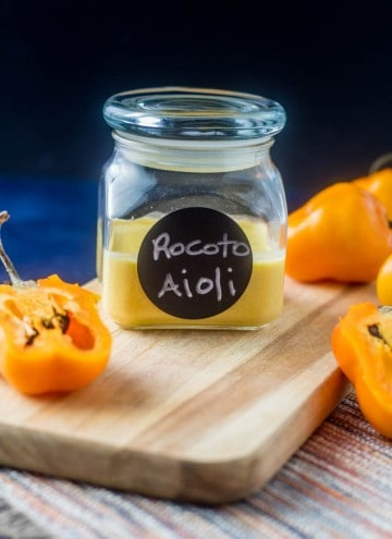 An air-tight jar with rocoto pepper aioli on a wood cutting board with fresh rocoto (manzano) peppers.