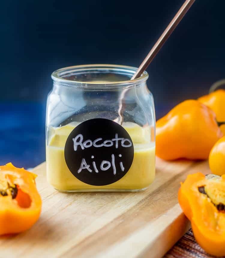 A jar of rocoto aioli with a copper spoon on a wood cutting board with yellow manzano peppers.