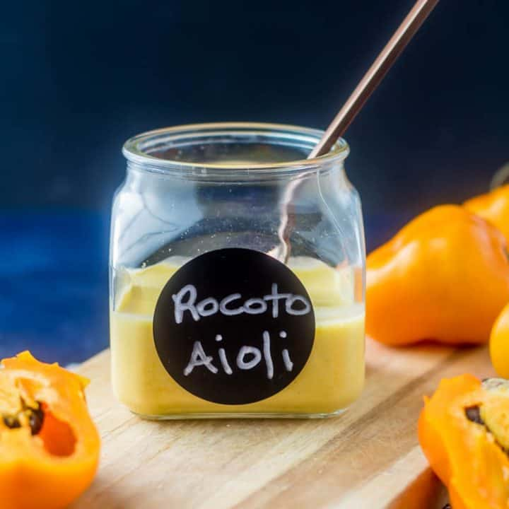 A jar of rocoto (aka manzano) pepper aioli with a copper spoon on a wooden cutting board with a few fresh peppers.