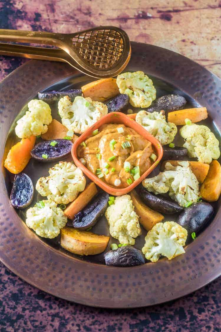 A copper tray with roasted cauliflower, sweet potatoes, and purple potatoes with an orange bowl of Mexican chorizo mayonnaise in the center.