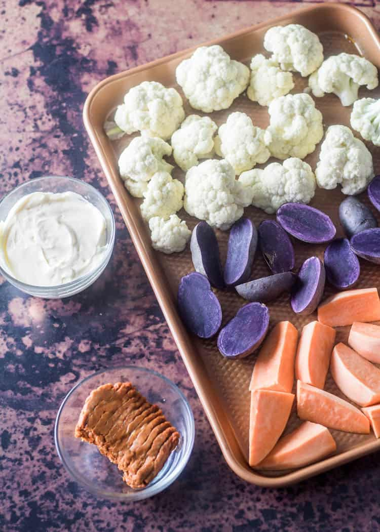 Ingredients for the recipe - A copper tray with cauliflower florets, sliced purple potatoes, wedges of sweet potatoes with mayonnaise, and lean chorizo ready to be prepared.