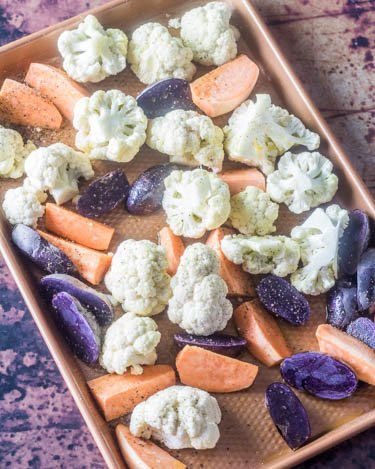 A copper baking sheet with the cauliflower, purple potatoes, sweet potatoes ready to go in the oven.