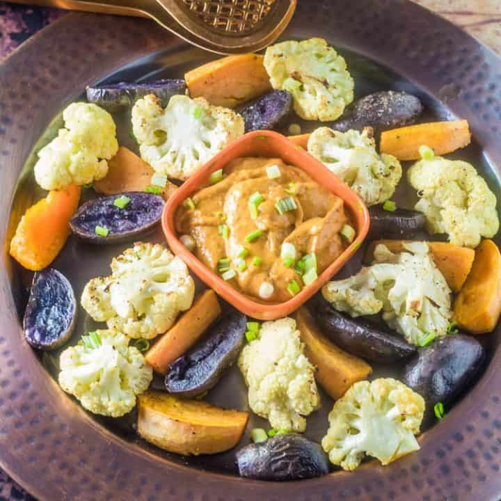 A copper tray with roasted cauliflower, sweet potatoes, purple potatoes with a square orange bowl of chorizo mayonnaise.