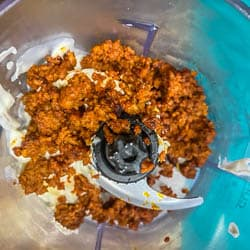 A small food processor with browned chorizo and mayonnaise before it is blended.